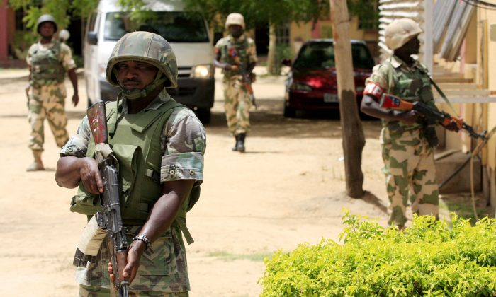 Nigerian soldiers stand guard at the offices of the state-run Nigerian Television Authority in Maiduguri, Nigeria, in this file photo taken June 6, 2013. (Jon Gambrell, File/AP Photo)