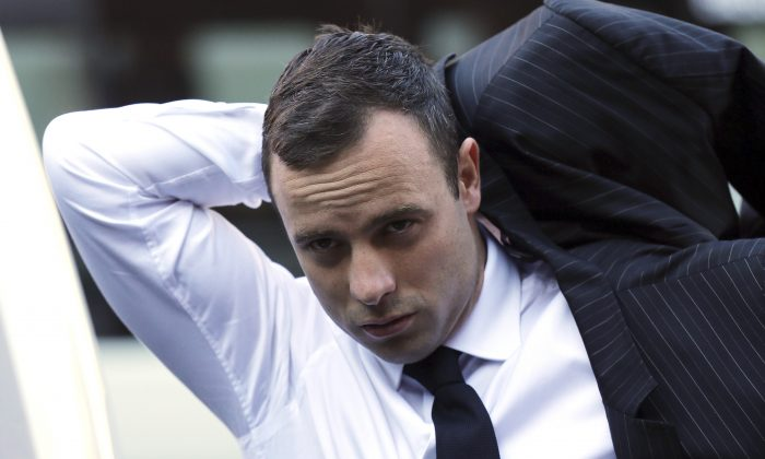 Oscar Pistorius puts on his jacket as he arrives at the high court in Pretoria, South Africa, on April 11, 2014. (AP Photo/Themba Hadebe)