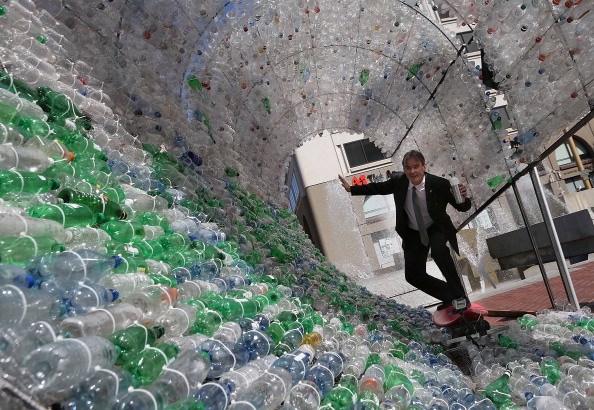 A man pretends to ride a surfboard as he poses for a photo inside a 14-foot wave made of plastic bottles on March 22, 2013 in San Francisco, California. (Justin Sullivan/Getty Images)
