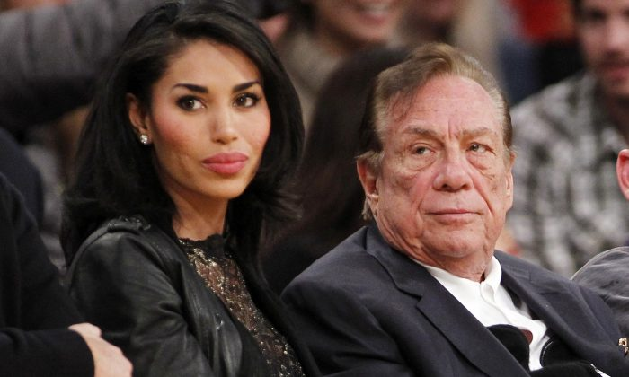 In this Dec. 19, 2010, file photo, Los Angeles Clippers owner Donald Sterling, right, and V. Stiviano, left, watch the Clippers play the Los Angeles Lakers during an NBA preseason basketball game in Los Angeles. (AP Photo/Danny Moloshok, File)