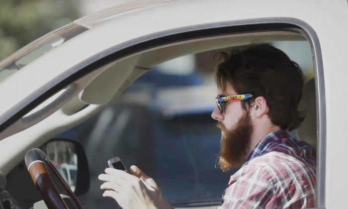 A man works his phone as he drives through traffic. Distracted driving now kills more people than impaired driving in at least four provinces. (AP Photo/LM Otero)