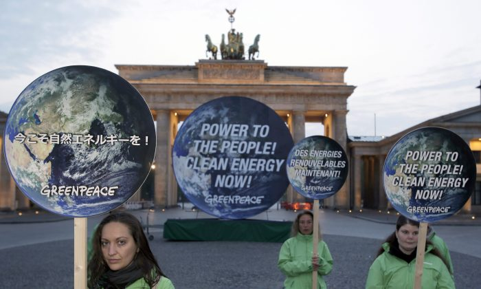 Greenpeace activists pose with posters in front of the Brandenburg Gate in Berlin, Germany, on April 13, 2014 to support clean energy. A Canadian study analyzing temperature data since 1500 all but rules out the possibility that global warming in the industrial era is just a natural fluctuation in the earth's climate. (AP Photo/Michael Sohn)