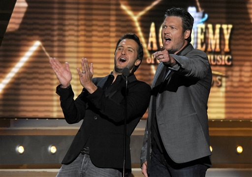 In this April 7, 2013 file photo, Luke Bryan, left, and Blake Shelton speak on stage at the 48th Annual Academy of Country Music Awards at the MGM Grand Garden Arena in Las Vegas. The 2014 Academy of Country Music Awards in Las Vegas will air live Sunday night, April 6, 2014, from 8-11 p.m. EDT on CBS. Several awards, including top honor entertainer of the year, will be announced during the broadcast, to be hosted by Blake Shelton and Luke Bryan. Shelton, Bryan, George Strait, Miranda Lambert, Jason Aldean, Keith Urban, Tim McGraw, Shakira and Stevie Nicks are scheduled to perform. (Chris Pizzello/Invision/AP, File)