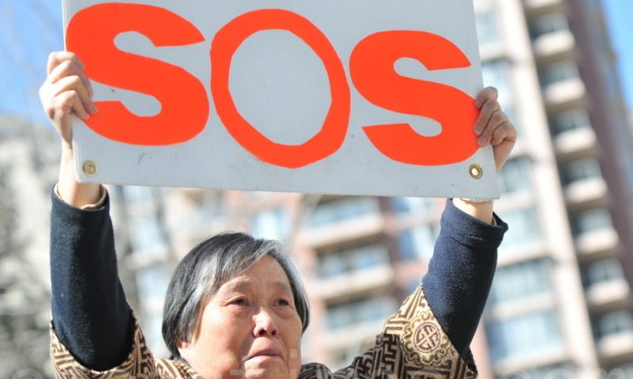 Huang Jinling holds an SOS sign at a press conference in Calgary on April 15, 2014 calling for help to rescue her daughter Chen Yinghua from a detention centre in China where she is said to be near death from a hunger strike. (Wu Weilin/Epoch Times)