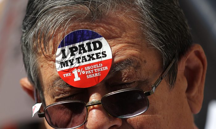 A protester wears stickers on his face during a tax day demonstration in front of the James A. Farley Post Office in New York on April 17, 2012. (Justin Sullivan/Getty Images)