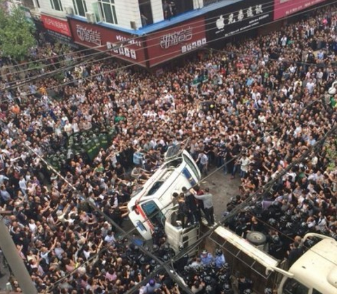 The angry crowd turns an ambulance on its side in Wenzhou City of Zhejiang Province on April 19. Over 1,000 people besieged five chengguan officers after they assaulted an onlooker. (Weibo)