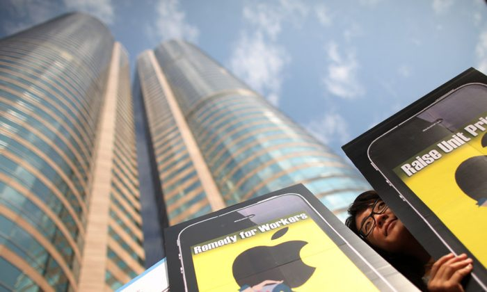 A woman holds a banner outside the Hong Kong stock exchange on October 15, 2011, calling for better conditions for factory workers making Apple products during a protest. (Ed Jones/AFP/Getty Images)