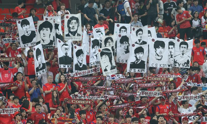 Soccer fans hold up portraits of South Korean national soccer team players before a friendly soccer match between South Korea and Tunisia at World Cup stadium in Seoul, South Korea, Wednesday, May 28, 2014. South Korea will play against Belgium, Russia and Algeria in Group H of the World Cup 2014 in Brazil. (AP Photo/Ahn Young-joon)