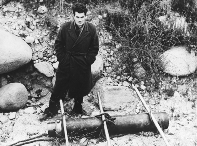 """John Whiteside """"Jack"""" Parsons standing above a jet-assisted take off canister at Jet Propulsion Laboratory's test site in the Arroyo Seco, L.A., on June 4, 1943. (NASA/JPL)"""