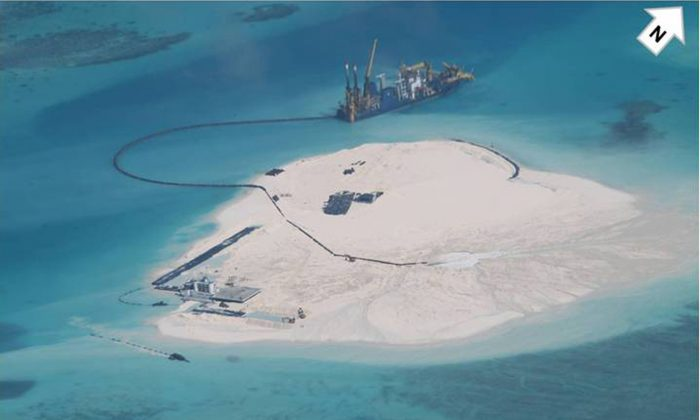 In this photo taken Feb. 25, 2014 by surveillance planes and released Thursday, May 15, 2014, by the Philippine Department of Foreign Affairs, a Chinese vessel, top center, is used to expand structures and land on the Johnson Reef, called Mabini by the Philippines and Chigua by China, at the Spratly Islands at South China Sea, Philippines. (AP Photo/Philippine Department of Foreign Affairs)