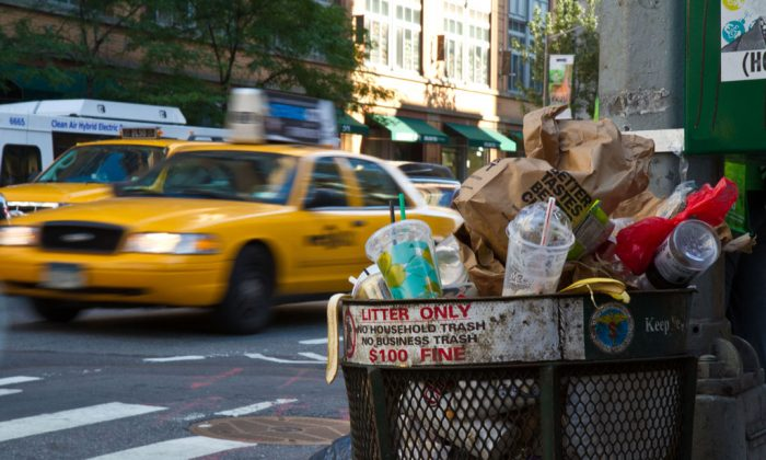 A trash can full of garbage is on Sixth Avenue right before it was emptied by a sanitation truck, in New York City, in this file photo. (Benjamin Chasteen/Epoch Times)