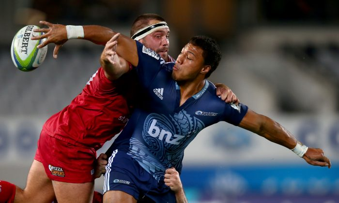 Blues winger George Moala offloads in the tackle of Reds hooker James Hanson during their Round 12 Super Rugby match on Friday May 2, 2014. (Phil Walter/Getty Images)