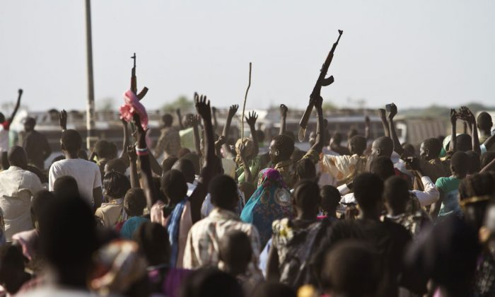 A Sudan People's Liberation Army (SPLA) soldier waves his AK-47 as soldiers celebrate alongside Internally Displaced People (IDP) outside the United Nations Mission in the Republic of South Sudan (UNMISS) base in Malakal after the SPLA claimed it had recaptured the town from rebels on March 19, 2014. (Ivan Lieman/AFP/Getty Images)