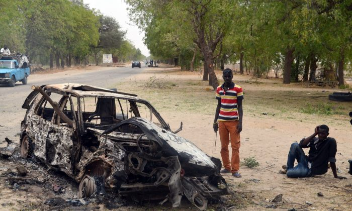 People stand by the wreckage of a car that has been blown up by suspected Boko Haram militants in Nigeria's troubled northeastern city of Maiduguri on March 25, 2014. (AFP/Getty Images)