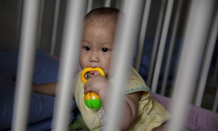 A young orphaned Chinese girl sits in a crib at a foster care center  in Beijing, China, on April 2, 2014. (Kevin Frayer/Getty Images)