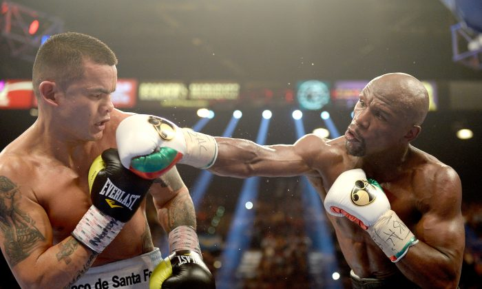 Floyd Mayweather Jr. knocks back Marcos Maidana during their WBC/WBA welterweight unification fight at the MGM Grand Garden Arena on May 3, 2014 in Las Vegas, Nevada. Mayweather took Maidana's title with a majority-decision victory. (Harry How/Getty Images)