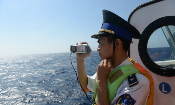 This picture taken on May 14, 2014 shows a Vietnamese coast guard officer taking pictures of a Chinese coast guard vessel near China's oil drilling rig in disputed waters in the South China Sea. (Hoang Dinh Nam/AFP/Getty Images)