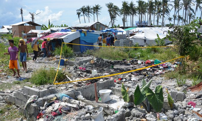 In this photo released by the City Mayor's Office of Tacloban City, a yellow tape is placed around the burnt remains of a tent that was razed by a fire early Wednesday, May 28, 2014 at a tent city in Tacloban, Leyte province in central  Philippines. An overnight fire razed a tent used as a temporary shelter by the survivors, killing a woman and five of her children, including a 4-month-old girl, officials in a central Philippine city devastated by the massive storm said Wednesday. The tragedy highlights the slow progress in the resettlement of tens of thousands of survivors of Haiyan, one of the world's strongest typhoons to make landfall November 8, 2013. The tents were donated by U.N. relief agencies after Typhoon Haiyan devastated Tacloban city and other provinces in central Philippines.(AP Photo/Tacloban City Mayor's Office)