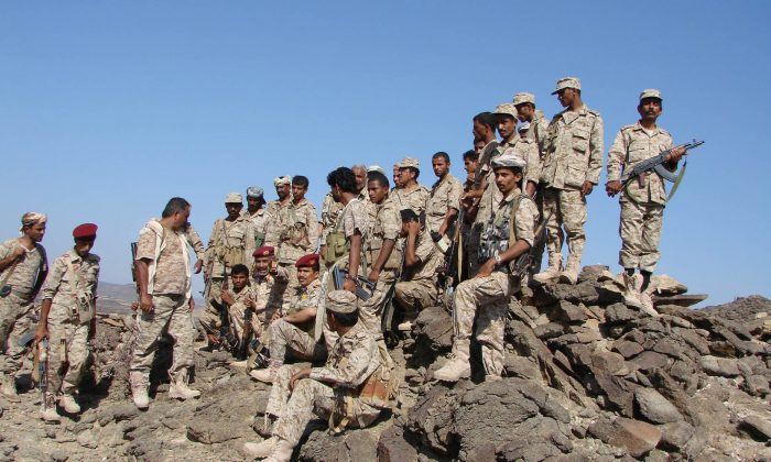 In this handout photo provided by Yemen's Defense Ministry, Yemeni troops take position during the fight against al-Qaida militants in the southern province of Shabwa, Yemen, Wednesday, April 30, 2014. Yemeni military on Tuesday, April 29, launched a major offensive targeting al-Qaida hideouts and strongholds, killing at least eight suspected militants, security officials said. (AP Photo/Yemen's Defense Ministry)