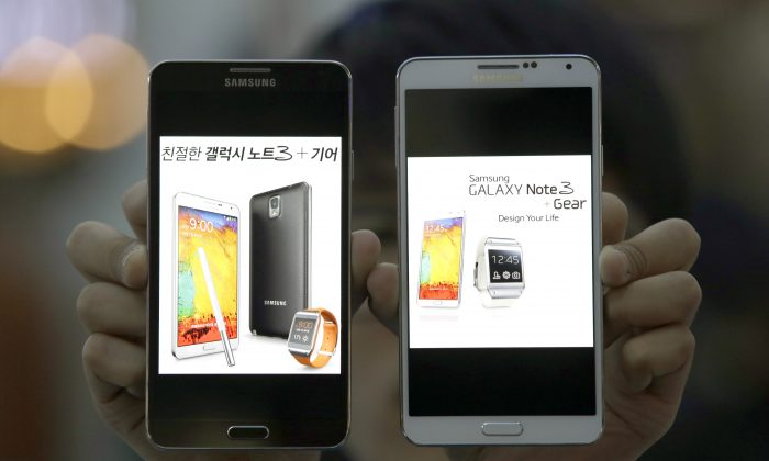 An employee of Samsung Electronics holds two Galaxy Note 3 smartphones for photos at a train station in Seoul, South Korea, Wednesday, Oct. 23, 2013. (AP Photo/Lee Jin-man)