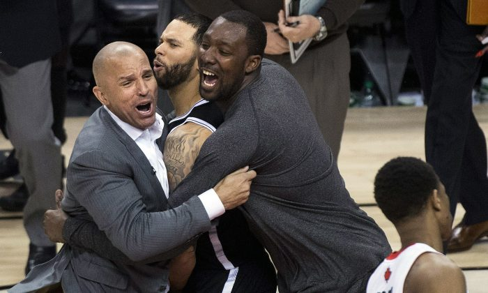 Brooklyn Nets head coach Jason Kidd (L) and teammates Deron Williams (C) and Andray Blatche react after defeating the Toronto Raptors in Game 7 of the 2013-14 NBA playoffs. (AP Photo/The Canadian Press, Nathan Denette)