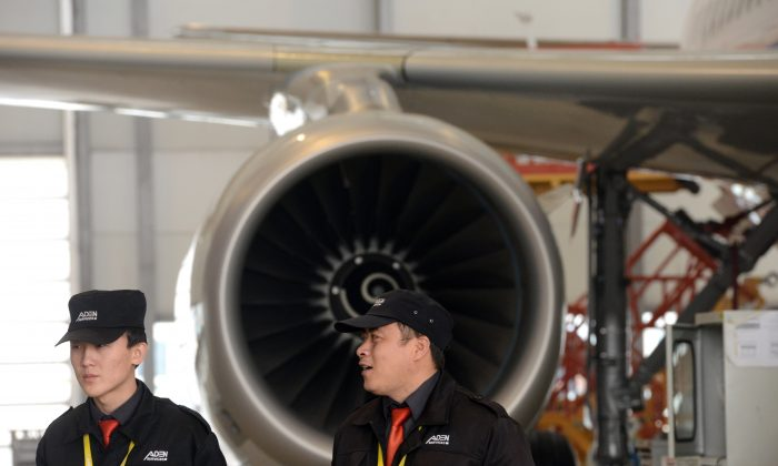 Chinese security guards stand near an Airbus A320 being assembled at the Airbus assembly plant in Tianjin. China is purchasing European aerospace companies to advance its aerospace industry. (GOH CHAI HIN/AFP/Getty Images)