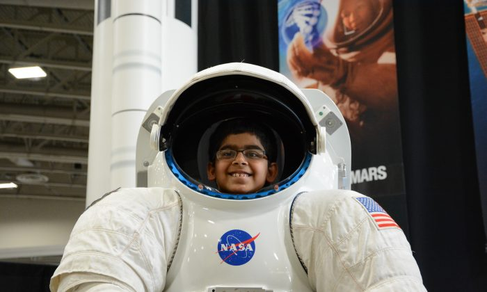 A future astronaut? A child enjoys a NASA display at the USA Science & Engineering Festival in Washington, D.C. (Du Won Kang/Epoch Times)