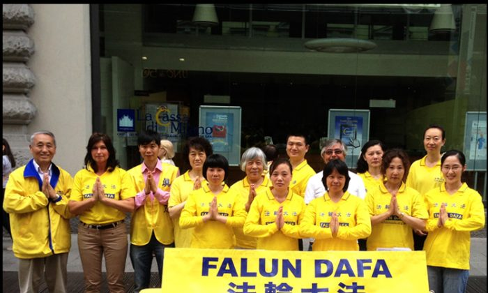"Falun Dafa practitioners pose in the respectful posture of ""heshi,"" in Milan, Italy on May 13, 2014. (Epoch Times)"