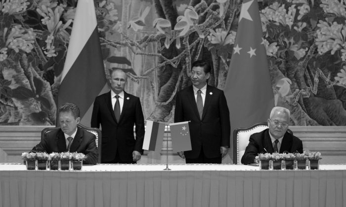 China's President Xi Jinping (back R) and Russia's President Vladimir Putin (back L) attend an agreement signing ceremony in Shanghai on May 21, 2014, with Gazprom CEO Alexei Miller (front L) and Chinese state energy giant CNPC Chairman Zhou Jiping (front R) signing an agreement. (Alexey Druzhinin/AFP/Getty Images)