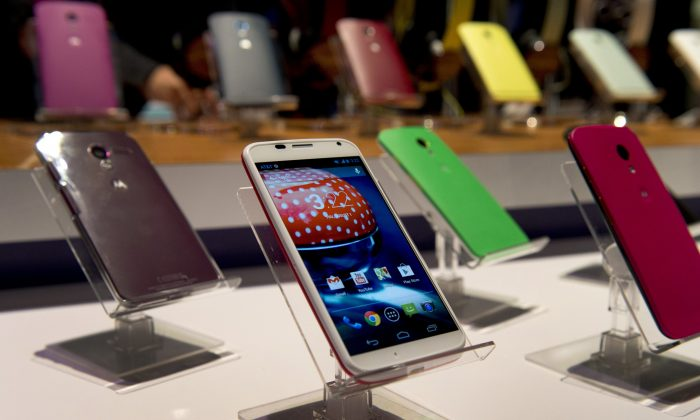 Motorola Mobility's Moto X smartphone is displayed in different colors at a a news conference in New York, Aug. 1, 2013. Apple and Google, which owns Motorola, have agreed to drop all pending patent lawsuits related to smartphones.   (Don Emmert/AFP/Getty Images)