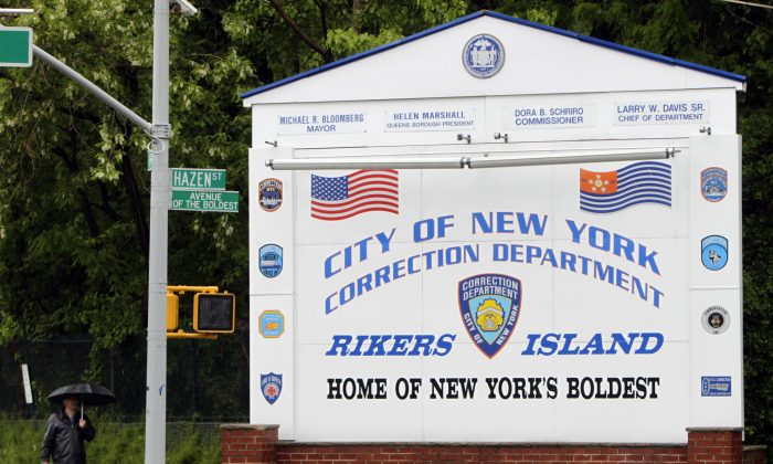In this May 17, 2011, file photo, a man walks near the sign at the entrance to the Rikers Island jail in New York. (AP Photo/Seth Wenig, File)