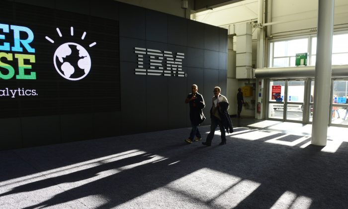 Men pass by the IBM booth on the eve of the start of the 2014 CeBIT technology trade fair on March 9, 2014 in Hanover, central Germany. (John MacDougall/AFP/Getty Images)