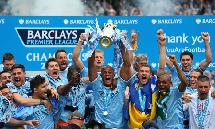 Vincent Kompany of Manchester City lifts the Premier League trophy in celebration along with his teammates at the Etihad Stadium on May 11, 2014 in Manchester, England. (Alex Livesey/Getty Images)