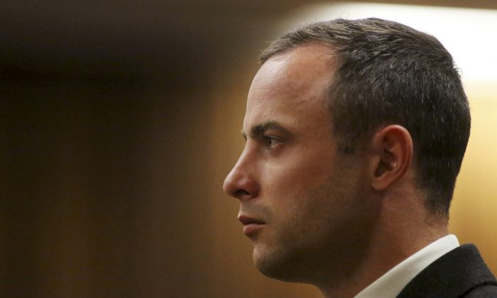 Oscar Pistorius listens as a court ruling is handed down that he would undergo psychiatric evaluation in Pretoria, South Africa, Tuesday, May 20, 2014. (AP Photo/Siphiwe Sibeko, Pool)