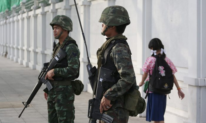 A school girl makes her way past Thai soldiers guarding at a street corner in Bangkok, Thailand Friday, May 30, 2014. (AP Photo/Apichart Weerawong)