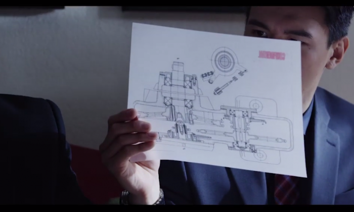 """Actors portraying Chinese spies in a new FBI film, """"The Company Man: Protecting America's Secrets,"""" examine design documents from a U.S. company. The FBI is making films to educate the public on methods used by foreign spies. (Screenshot from FBI film)"""