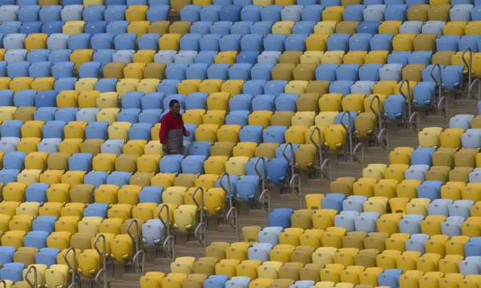 A worker walks amid the seats of the Maracana stadium during a press tour, in Rio de Janeiro, Brazil, Monday, May 26, 2014. Brazil will host the World Cup soccer tournament starting on 12 June and Maracana stadium will host the World Cup Final match on July 13. (AP Photo/Silvia Izquierdo)