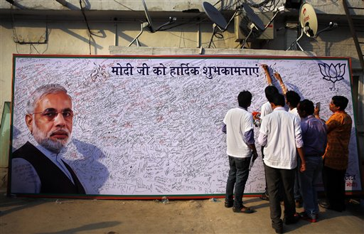 Bharatiya Janata Party (BJP) supporters write congratulatory messages for their leader Narendra Modi on a giant board at their party headquarters in New Delhi, India, Friday, May 16, 2014. Modi will be India's next prime minister, winning the most decisive election victory the country has seen in more than a quarter century and sweeping the long-dominant Congress party from power, partial results showed Friday. (AP Photo /Manish Swarup)