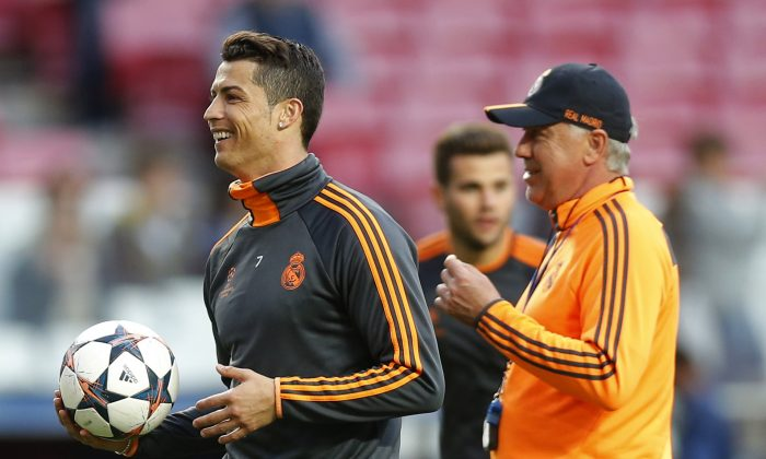 Real's coach Carlo Ancelotti,  right, smiles as Real's Cristiano Ronaldo, left, walks, during a training session ahead of Saturday's Champions League final soccer match between Real Madrid and Atletico Madrid, in Luz stadium in Lisbon, Portugal, Friday, May 23, 2014. (AP Photo/Daniel Ochoa de Olza)