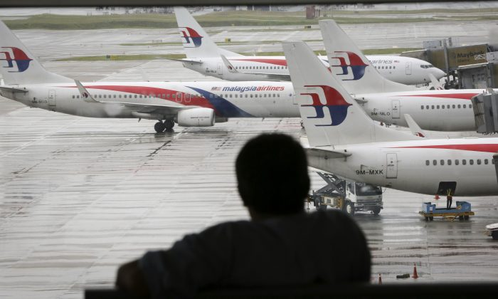 A visitor looks out from the viewing gallery as Malaysia Airlines aircraft sit on the tarmac at the Kuala Lumpur International Airport (KLIA) in Sepang, Malaysia, Tuesday, May 27, 2014. The Malaysian government on Tuesday released 45 pages of raw satellite data it used to determine the flight path of the missing jetliner, information long sought after by some of the relatives of the 239 people on board the plane. (AP Photo/Vincent Thian)