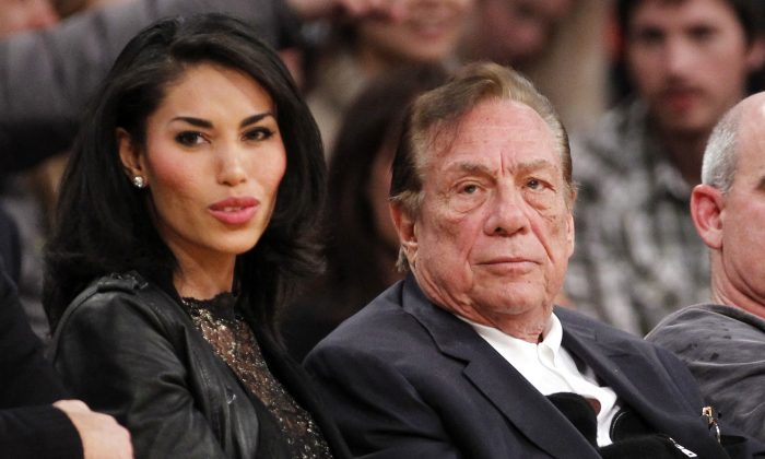 In this Dec. 19, 2010, file photo, Los Angeles Clippers owner Donald Sterling, third right, sits with V. Stiviano, left, as  they watch the Clippers play the Los Angeles Lakers during an NBA preseason basketball game in Los Angeles. (AP Photo/Danny Moloshok, File)