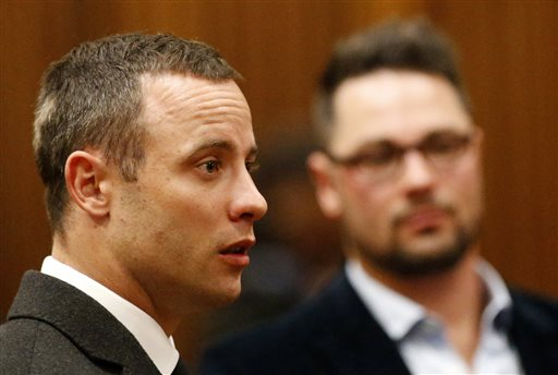 Oscar Pistorius, listens as a court ruling is handed down that he would undergo psychiatric evaluation in Pretoria, South Africa, Tuesday, May 20, 2014. Pistorius is charged with the shooting death of his girlfriend Reeva Steenkamp on Valentine's Day in 2013. At back right is brother Carl Pistorius. (AP Photo/Siphiwe Sibeko, Pool)