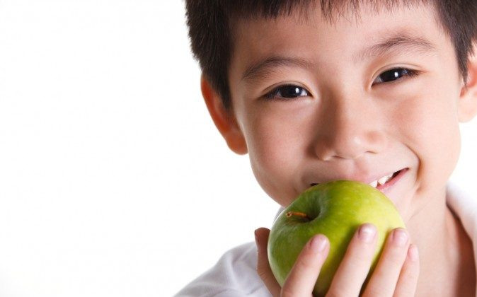 Boy eats an apple. Apples contain the most pesticide residues, according to the Environmental Working Group (EWS).