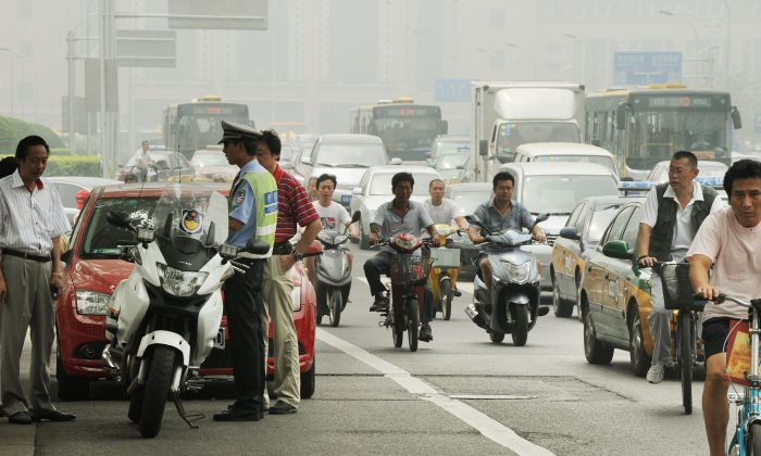 A Chinese policeman tries to resolve a traffic dispute between the driver of a luxury Porsche and another car after an accident in Beijing on Aug. 9, 2011. For the past decade China has had the highest annual number of traffic accident deaths in the world. (Mark Ralston/AFP/Getty Images)