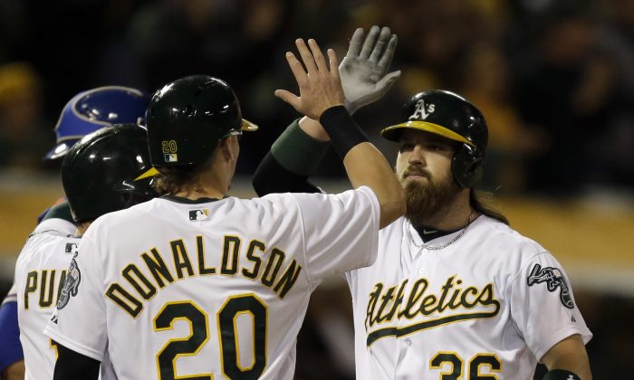 Oakland Athletics' Josh Donaldson, left, congratulates Derek Norris, right, after Norris hit a three-run home run off off Texas Rangers' Shawn Tolleson in the sixth inning of a baseball game Tuesday, June 17, 2014, in Oakland, Calif. (AP Photo/Ben Margot)