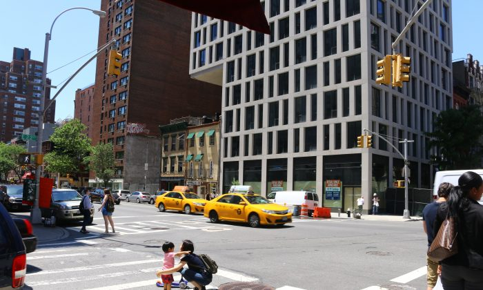 Mother and child cross the dangerous 3rd Avenue and East 22nd Street intersection, New York, June 16, 2014. (Brendon Fallon/Epoch Times)