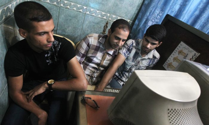 Iraqi men use a computer at an Internet cafe in Baghdad on June 26, 2012. (Ahmad Al-Rubaye/AFP/Getty Images)