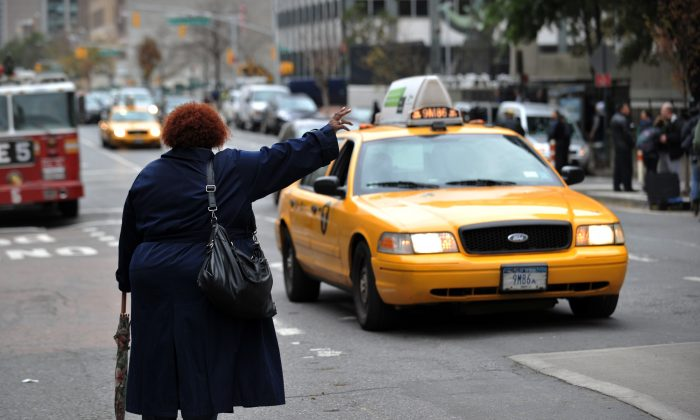 A woman tries to hail a taxi on First Avenue October 31, 2012 in New York. (Stan Honda/AFP/Getty Images)