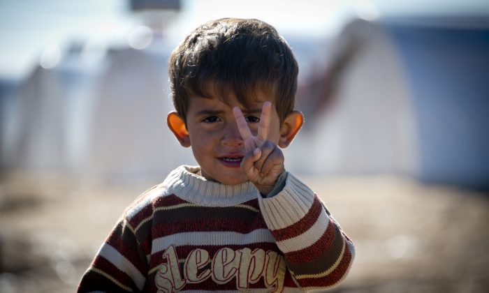 Standing in front of a row of plastic tents a young boy refugee flashes the V-sign in a refugee camp on the border between Syria and Turkey near the northern city of Azaz on December 5, 2012. (AFP PHOTO / ODD ANDERSEN)