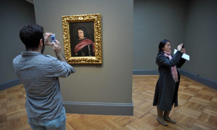 "People take photographs near Spanish artist Diego Velázquez's ""Portrait of Duke Francesco I d'Este"" 1638 at The Metropolitan Museum of Art, April 15, 2013, in New York. (Stan Honda/AFP/Getty Images)"